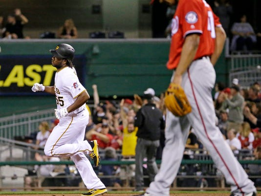 Pittsburgh Pirates' Josh Bell, left, rounds first after hitting a solo home run off Washington Nationals starting pitcher Joe Ross, right, in the third inning of a baseball game in Pittsburgh, Saturday, Sept. 24, 2016. (AP Photo/Gene J. Puskar)