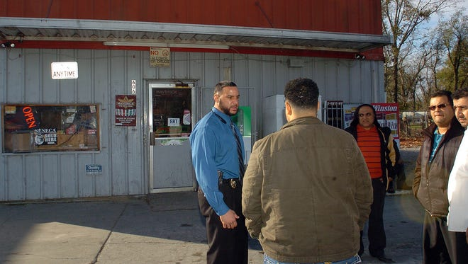Detective Graig LeBlanc, left, of the Opelousas Police Department investigates a homicide that occurred around 6 p.m. Tuesday at Bikini Betty's convenience store located on South Railroad Avenue.