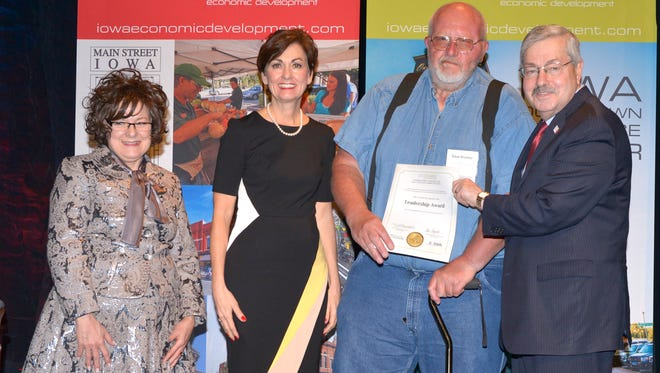 Belle Plaine's Dave Kramer receives a Main Street Iowa Award from Debi Durham, director of the Iowa Economic Development Authority, Lt. Gov. Kim Reynolds and Gov. Terry Branstad and an awards ceremony in April in Des Moines.
