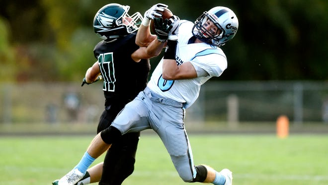 Lansing Catholic's Alex Bres, right, catches a pass as Williamston's Mason Bamfield defends during the first quarter on Friday, Sept. 15, 2017, at Larkin-Nortman Memorial Field in Williamston.