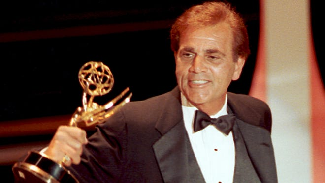 """In this Sept. 16, 1990, photo, actor Alex Rocco holds up his Emmy award for best supporting actor in a television comedy series for his role in """"The Famous Teddy Z,"""" during his acceptance speech at the 42nd Annual Primetime Emmy Awards in Pasadena, Calif."""
