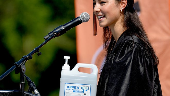 With a jug of hand sanitizer on the podium, class president Ciara Murphy delivers the student speech during commencement exercises at Wayland High School Saturday, July 25.