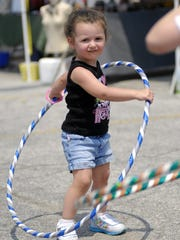 Emma Post, of Centerline, does her best to keep her hula hoop from falling during the Art on the River event.