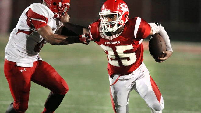 Fishers tailback Maurice Campbell grabs the face mask of Pike's Alon Harrison as he tries to break up field at Fishers High School on Friday, August 29, 2014. Pike beat Fishers 26-22.