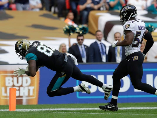 Jacksonville Jaguars tight end Marcedes Lewis (89) scores a touchdown in front of Baltimore Ravens linebacker Tyus Bowser during the first half of an NFL football game at Wembley Stadium in London, Sunday Sept. 24, 2017. (AP Photo/Matt Dunham)
