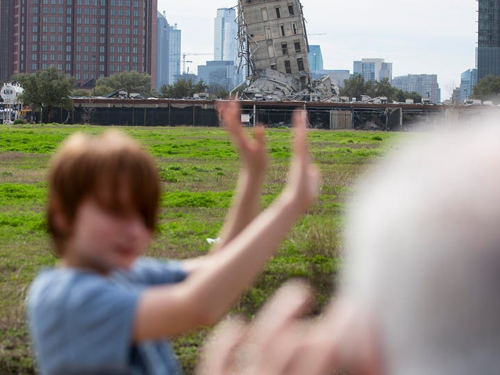 "Randy Gibson takes a photo of his son Andrew, 11, in front of the ""Leaning Tower of Dallas"" on Monday."