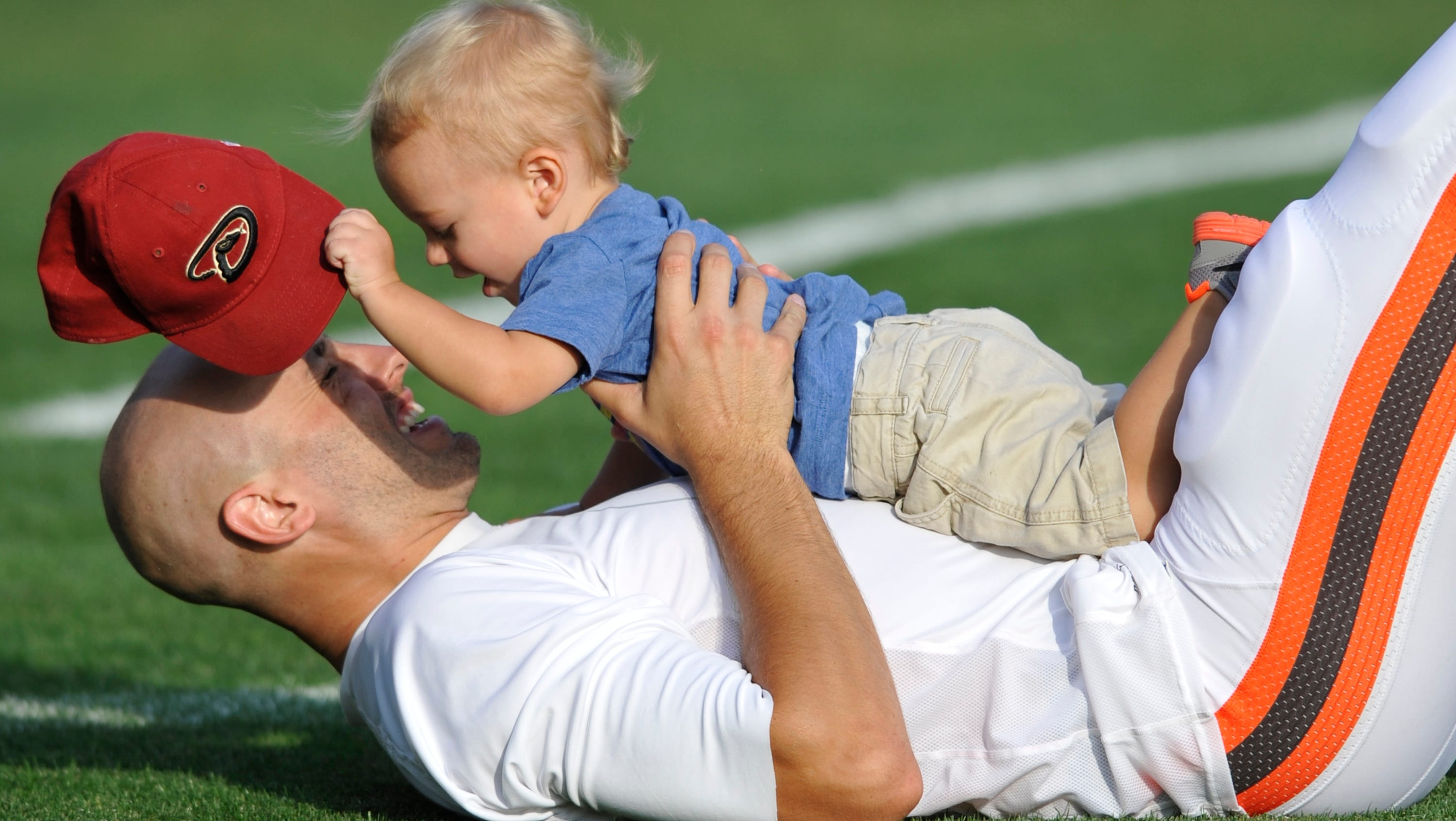 Cleveland Browns quarterback Brian Hoyer holds his son Garrett after practice during training camp at the NFL football team's facility in Berea, Ohio.