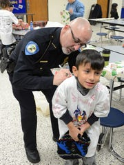Rich Van Boxtel of the Oneida Police Department signs Davian Gutierrez's shirt Saturday during the Shop with a Cop event in Ashwaubenon.