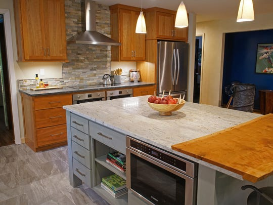The kitchen by Zoe Hewitt includes simple cabintry, two kinds of honed granite and a floor of grouted luxury vinyl tiles.