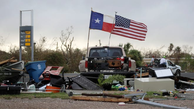 The Texas state flag and American flag wave in the wind over an area of debris left behind in the wake of Hurricane Harvey, Sunday, Aug. 27, 2017, in Rockport, Texas.