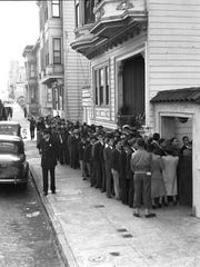 """People in line to register for """"evacuation"""" at a """"civil control"""" station in San Francisco on  April 25, 1942. Inside they will receive identification numbers and instructions for """"evacuation day."""" This photo is featured in an exhibit on Japanese internment at the FDR Presidential Library and Museum in Hyde Park."""