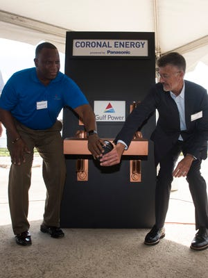 From left, Michael Burroughs, Gulf Power vice president and senior production officer, and Coronal Energy President Ed Feo symbolically flip the switch to begin producing power at the new solar facility off Saufley Field Road on Tuesday, Aug. 22, 2017.  The new facility is capable of generating enough energy to power an estimated 7,400 homes in Escambia County.