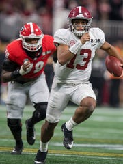 Alabama quarterback Tua Tagovailoa (13) carries against Georgia in the College Football Playoff National Championship Game in the Mercedes Benz Stadium in Atlanta, Ga., on January 8, 2018.