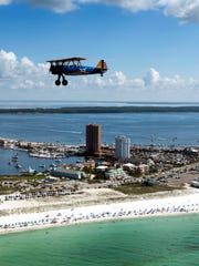A vintage Stearman biplane flies over Pensacola Beach during the Veterans Flight in 2018.