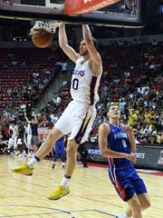 Lakers guard Sviatoslav Mykhailiuk dunks ahead of Pistons forward Henry Ellenson in a quarterfinal game of NBA summer league at the Thomas & Mack Center on July 15, 2018 in Las Vegas.