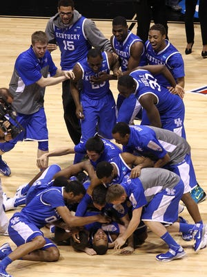 Kentucky players celebrate after a 3-pointer by Aaron Harrison clinched Sunday's game.