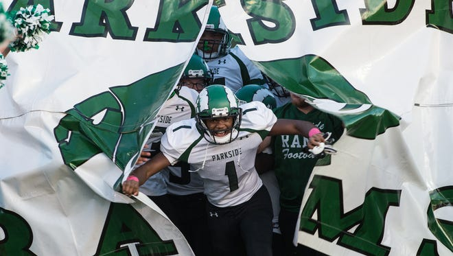 Parkside football players storm the field at the start of a game against James M. Bennett on Friday, Oct. 6, 2017.