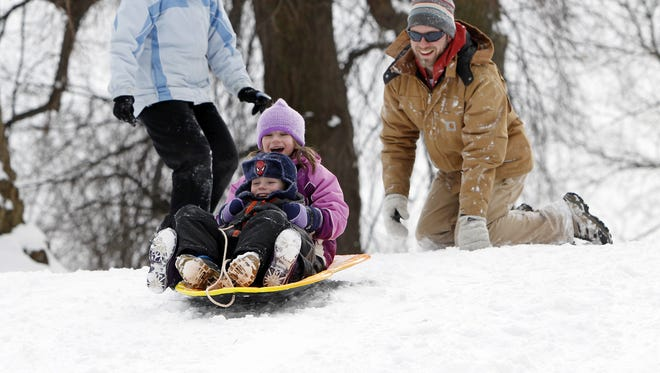 Hannah, 6, and Joe, 4, get a push down a sledding hill from mom and dad, Tammy and Andy Graupman on Jan. 26, 2014.