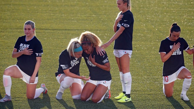 The Chicago Red Stars' Julie Ertz, second from left, holds Casey Short, center, while other players for the team kneel during the national anthem before an NWSL Challenge Cup match against the Washington Spirit.