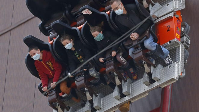 In this May 23, 2020, file photo, people ride the Cannibal at Lagoon Amusement Park in Farmington, Utah. Amusement parks are adjusting everything from selling tickets to serving meals while trying to reassure the public and government leaders that they're safe to visit amid the coronavirus crisis and warnings against large gatherings.