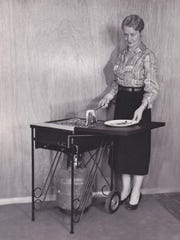 A woman demonstrates a LazyMan portable grill in this