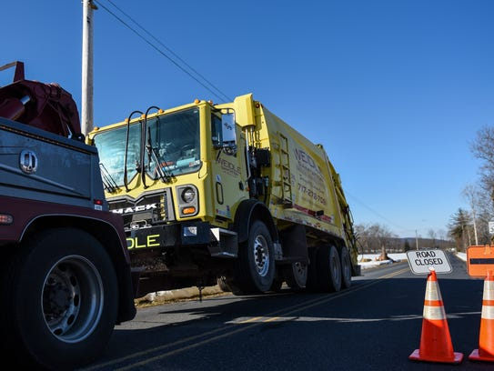 A tow truck hauls away a Weidle Sanitation truck that