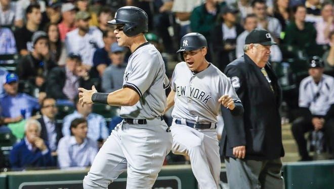 New York Yankees outfielder Jacoby Ellsbury (R) and New York Yankees outfielder Aaron Judge (L) celebrate as they both score on a double hit by New York Yankees designated hitter Gary Sanchez in the eighth inning of their MLB game against the Chicago White Sox.
