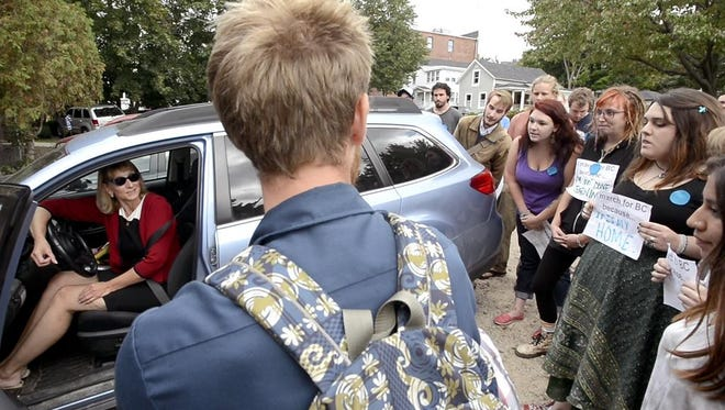 Burlington College President Christine Plunkett is blocked by students as she tries to leave a board meeting at the Lake Champlain Regional Chamber of Commerce office on Main Street in Burlington Friday morning.