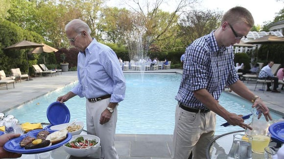 Vice President Joe Biden and University of Delaware men's basketball team member Kyle Anderson dig into the poolside barbecue as the team visits the Vice President's residence at the Naval Observatory after a stop at the White House, Thursday, May 8, 2014.