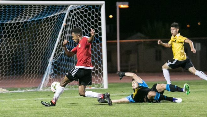 Forward Dennis Chin dribbles past the Phoenix College goalkeeper and scores in the second half of their preseason game on March 21.