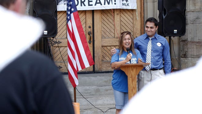 Cindy Garcia of Lincoln Park speaks to the crowd and is joined by Adonis Flores of Detroit during the Revive the Dream rally and march on August 24, 2013 at St. Anne's Church in Detroit. Flores is cautiously optimistic about Obama's executive order.