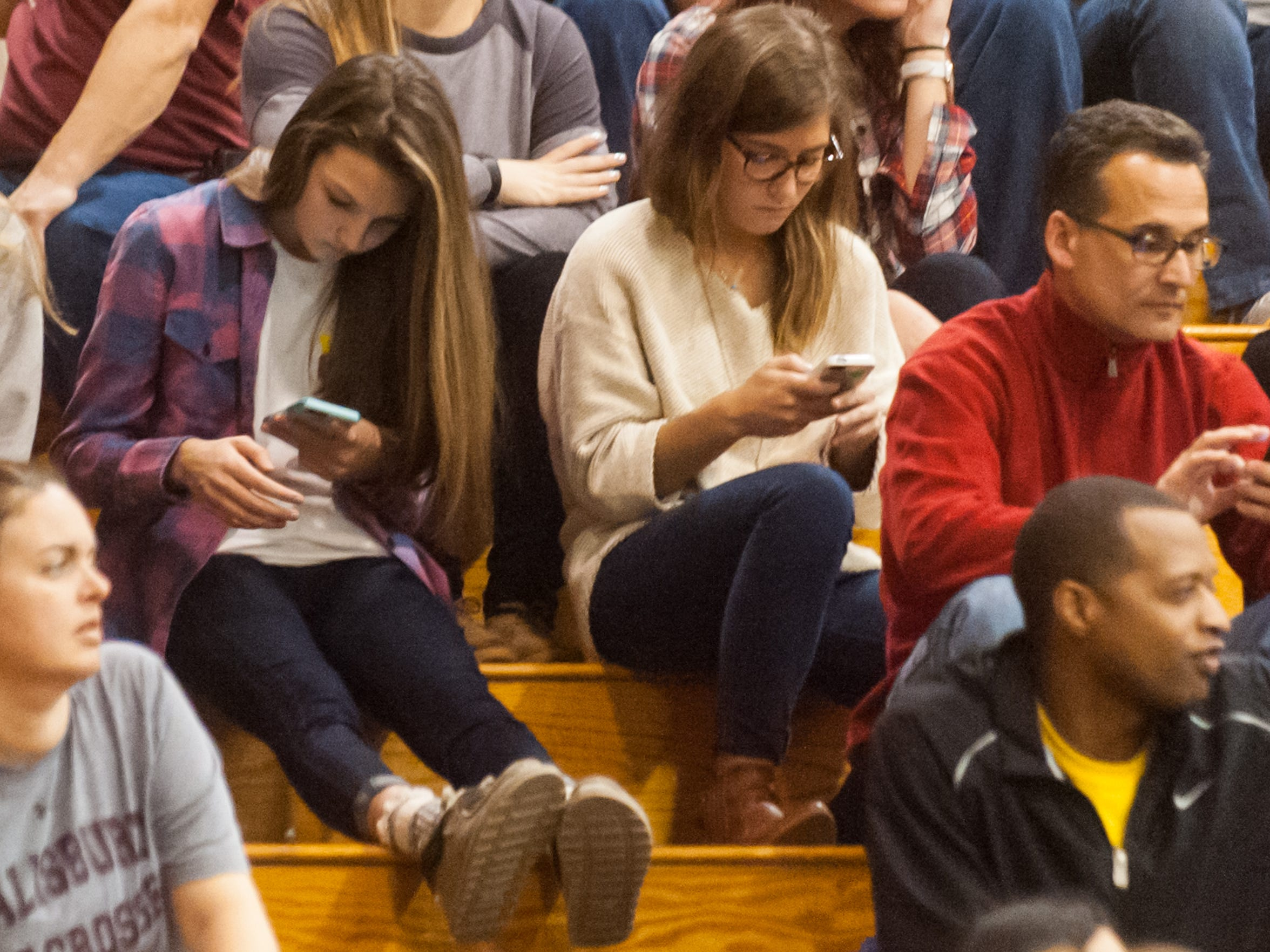 Fans check their cell phones during a Salisbury University basketball game on Saturday afternoon.