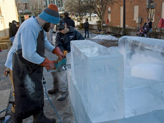 DiMartino Ice Company employees construct the popular ice slide in a parking lot off South Main Street, Wednesday, January 25, 2017. The Chambersburg festival kicks off Thursday evening.
