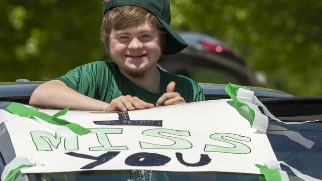 HOLDEN - Rising senior Chris Poplawski waves to teachers from a sunroof Monday during a reverse parade for students of Wachusett Regional High School. About 50 teachers and staff lined the route. Organizers said they especially wanted to show some love for special education students, who teachers say have been disproportionately affected by school shutdowns.