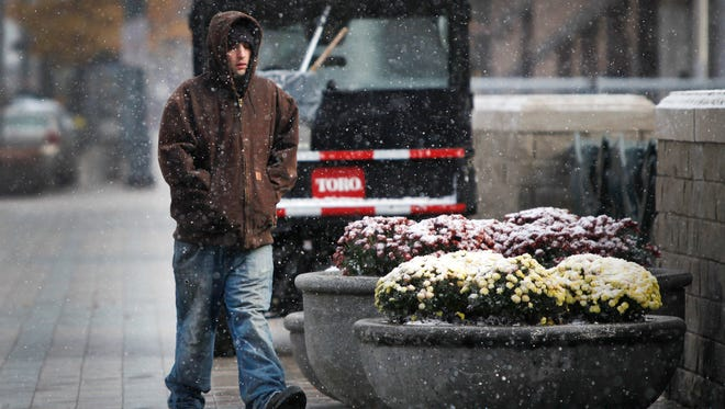 Dominic Callea of Rochester was bundled for the cold blast of snowflakes that fell Friday on Main Street downtown as he walked to his job at the Blue Cross Arena.