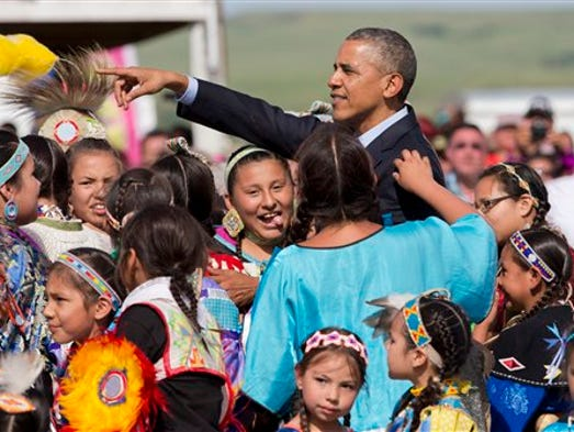 President Barack Obama,  joins children of the Standing Rock Sioux Tribal Nation, in Cannon Ball, N.D., Friday, June 13,  2014, during a Cannon Ball flag day celebration, at the Cannon Ball powwow grounds. It?s the president?s first trip to Indian Country as president and only the third such visit by a sitting president in almost 80 years.  (AP Photo/Manuel Balce Ceneta)