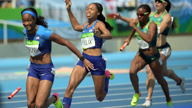 The United States' Allyson Felix and English Gardner drop the baton hand off during the women's 4x100m relay heats. It was ruled the team was interfered with and was given a redo and qualified with the top time for Friday's final.