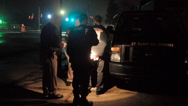 St. Clair County sheriff deputies cuff and put a suspect into a van to be transported to the St. Clair County Detention Center in 2012 at 3800 block of Lapeer Road in Port Huron Township.
