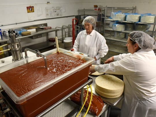 Sauce is added to pizzas Wednesday, Dec. 30 at Gourmet
