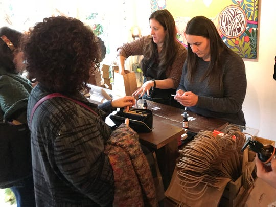 Sisters Nicci Silva, left, and Amy Rivera, help customers at their store, Dolly Moo, in Montclair, on Saturday.