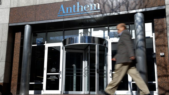 In this file photo, a man walks past health insurer Anthem's corporate headquarters in Indianapolis.