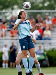 Lansing Catholic's Camille Coenen heads the ball against Flint Powers Catholic during their regional final, Friday, June 9, 2017, in Williamston. Lansing Catholic fell 5-0.