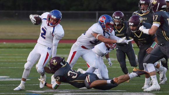 Carmel's Leonard Flocco tries to move the ball down the field as Arlington's E.J. Escoto, center, tackles him during Friday's game.