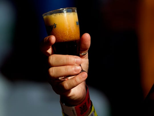 A beer fan holds a sample at the seventh annual Knoxville