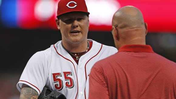 Reds-Indians. Former Cincinnati Reds starting pitcher Mat Latos (55) talks with Cincinnati Reds head trainer Paul Lessard about a thumb problem during the fifth inning of their game against the Cleveland Indians played at Great American Ball Park Wednesday Aug. 6, 2014.