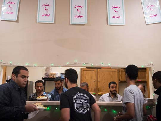 Men break their fast at Ramadan iftar, the daily meal