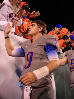Boise State Broncos quarterback Grant Hedrick (9) celebrates with Bronco fans from the stands after the Broncos' defeated the Brigham Young 55-20 at Albertsons Stadium.