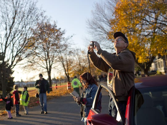 A man takes pictures as people gather to watch the implosion of the former DTE power plant Saturday, November 7, 2015 in Marysville.