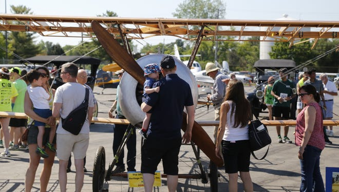 A father and son inspect a cross-sectioned biplane at Airport Day at the Ithaca Tompkins Regional Airport on Father's Day. Nearly 1,000 attended in all.