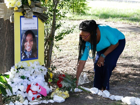 Jeanette Williams places a bouquet of roses at a memorial for Sandra Bland near Prairie View A&M University in Prairie View, Texas, on July 21, 2015. A state investigation of a white state trooper's actions in the arrest of Bland, a black motorist who later died in custody, found that the trooper, Brian Encinia, was rude toward Bland and failed to follow standard procedures in his handling of the woman.